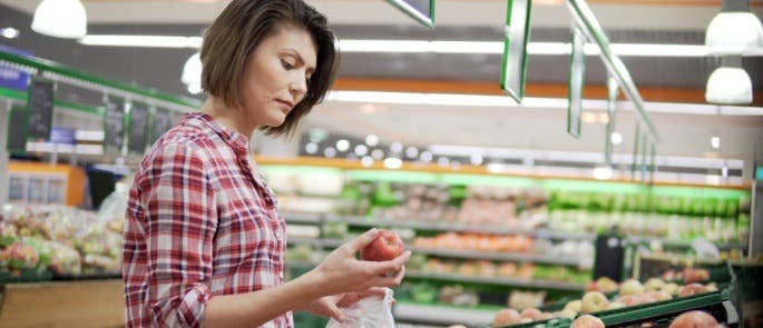 Brown haired woman in fruit and veg aisle of supermarket looking quizically at an apple in her hand.