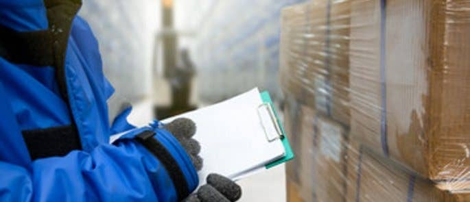 Close up of hands checking paperwork on a clipboard in front of wrapped packages inside a warehouse full of containers.