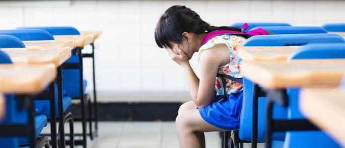 Sad schoolgirl sat down in classroom with head in hands