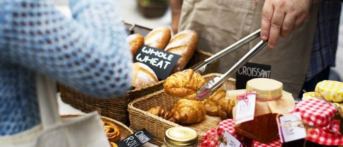 A man selling croissants and jam on a market stall