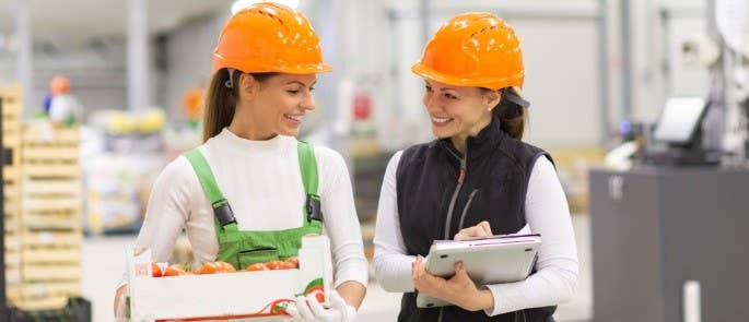 Two women in a food warehouse with clipboards