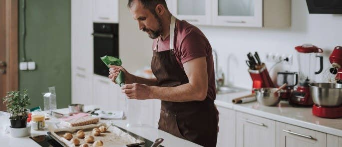 Man wearing an apron icing his cupcakes.