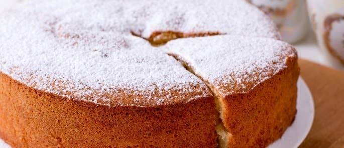 Close up of a Victoria sponge cake with icing sugar dusting.