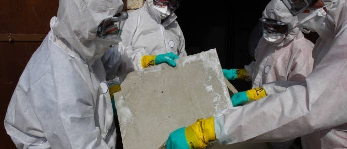 Asbestos removal experts putting asbestos in a bag
