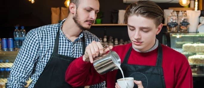Manager oversees young male worker making coffee for customer