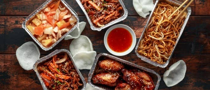 Chinese takeaway food including noodles and chicken in metal containers