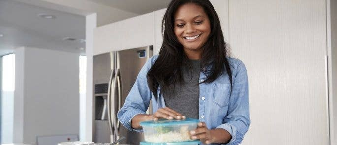 Woman in her kitchen at home putting leftover food into plastic containers