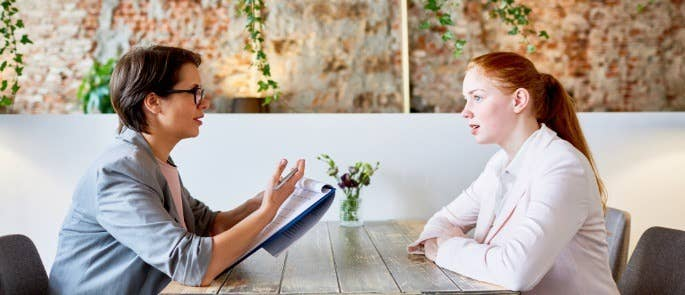 Female manager interviewing a young woman while sat across from each other at a table