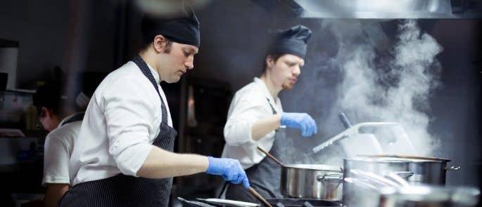 Two chefs working in a dark industrial kitchen