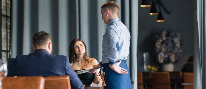 Waiter at a table taking the food orders of a couple