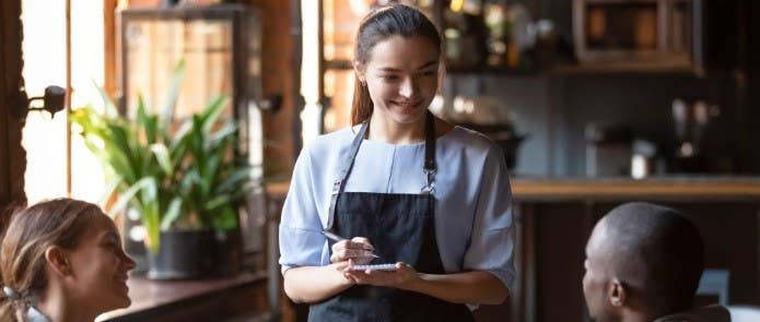 Waitress in a restaurant taking people's food orders