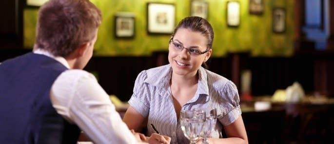 young woman interviews man for chef job