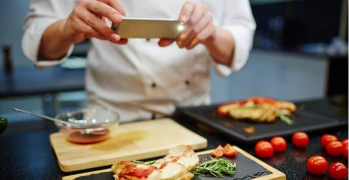 chef taking photo of food for restaurant social media
