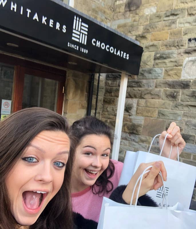 A & J leaving Whitakers Chocolates with goody bags