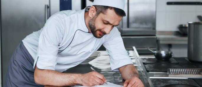 Head chef writing his risk assessment notes in the kitchen