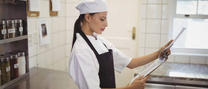 Chef reads risk assessment on clipboard while standing in her kitchen