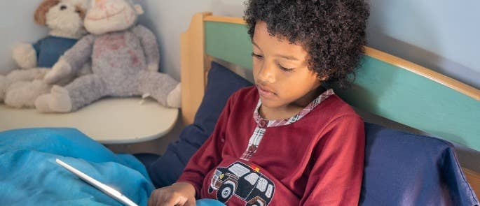 Boy laid in bed on tablet device