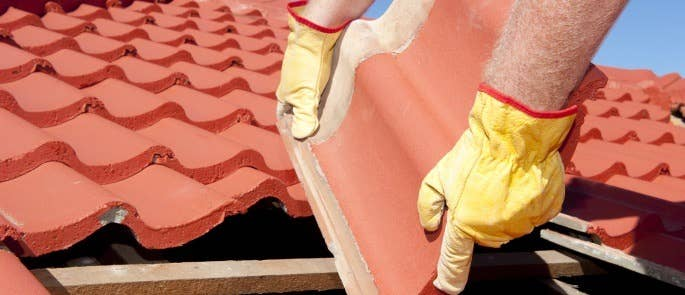 A man placing a roofing tile on an incomplete roof