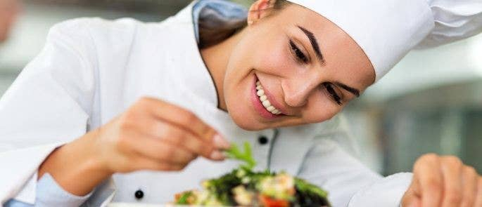 Female chef garnishing a dish