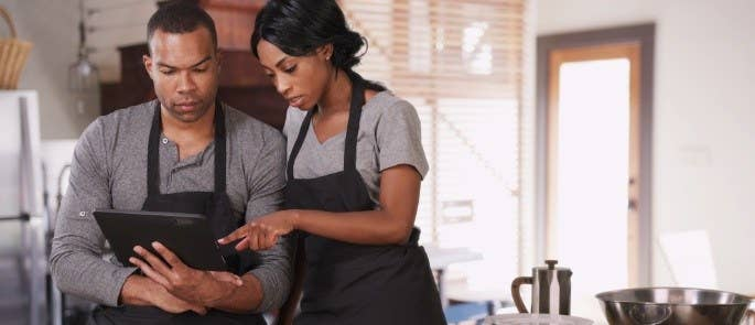 Two deli workers in aprons looking at a tablet