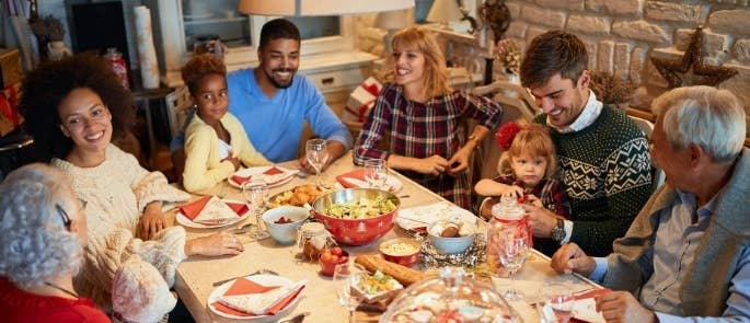 Large family of sitting round table after Christmas dinner talking and smiling