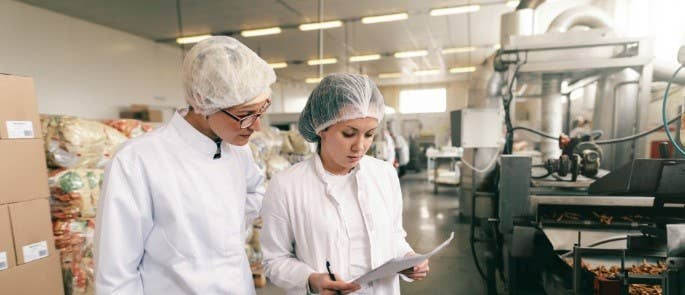 Two women check paperwork together in a food processing plant