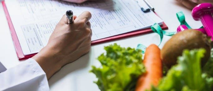 Close up shot of a nutrition plan with vegetables on the desk nearby