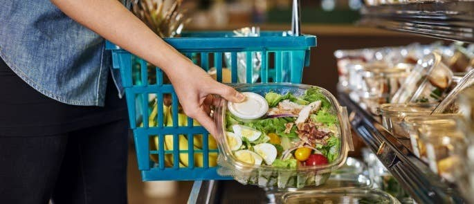 A customer selecting a pre-made salad and putting it into her basket