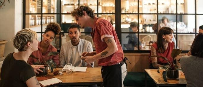 Waiter helping customers with allergen information