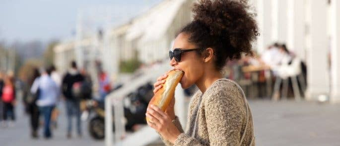 A woman eating a baguette