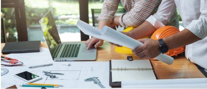 Construction managers work hard over blueprints