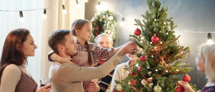 Family decorating a christmas tree together