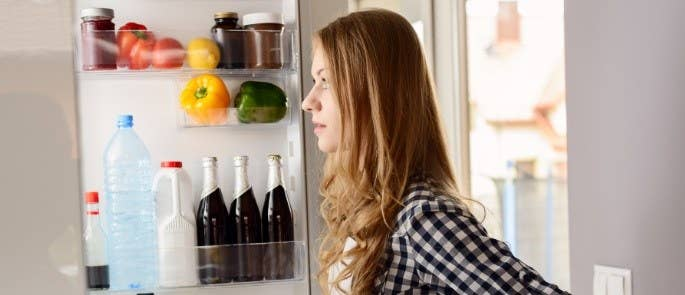 Young woman looks in fridge