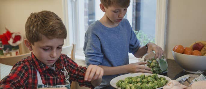 Two brothers prepare sprouts with cranberies for Christmas dinner