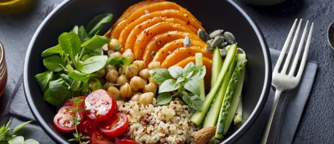 A salad with a variety of vegetables and grains