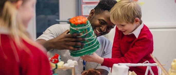 Male teacher helping primary school children with crafts