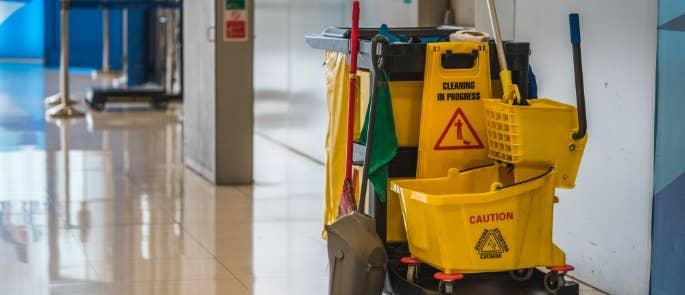 School cleaners trolley with equipment in school corridor