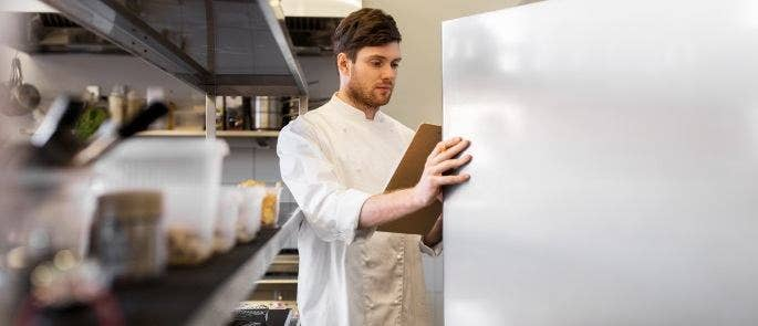 A chef wearing a chef jacket taking an inventory