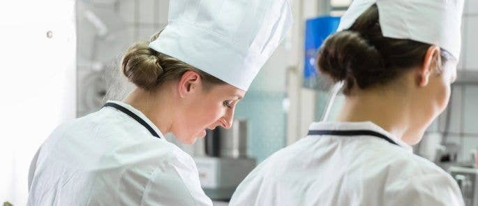 Two female chefs wearing hats in the kitchen