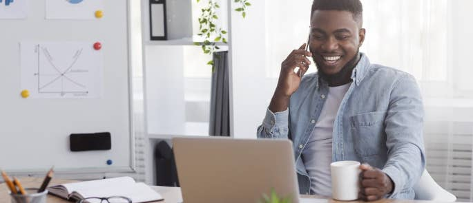 Man smiling whilst ringing a friend to boost morale