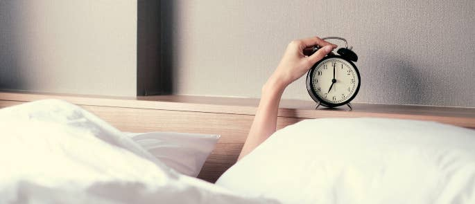 Woman turning off the alarm clock to get back to sleep