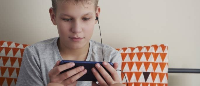 Young boy watching a video on his phone
