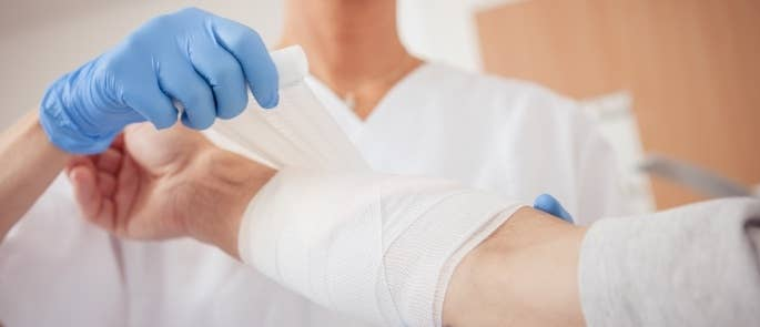 Healthcare worker putting a bandage on a patient