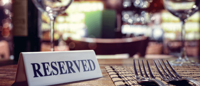 close up of a reserved sign on a set table in a restaurant.