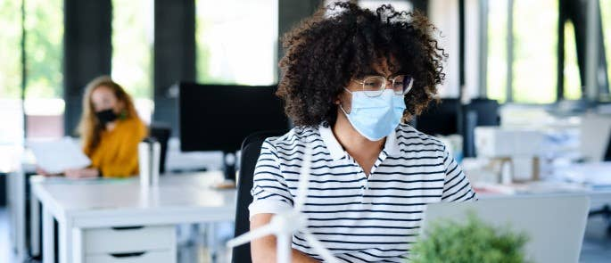 Young worker at office desk wearing a mask