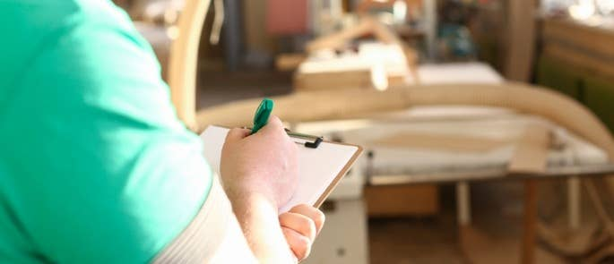 Employer carrying out risk assessment of workplace