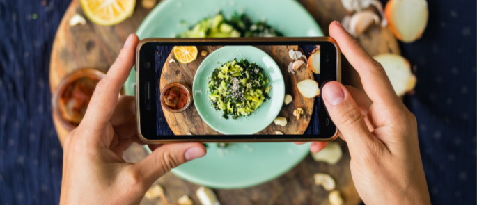 person taking social media image of food in a restaurant