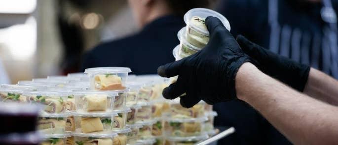 People wearing gloves to prepare food for takeaway