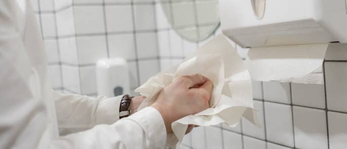 Worker drying their hands with disposable paper towels