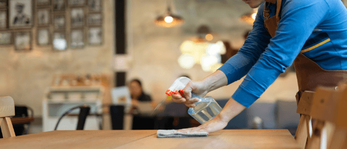 Waiter disinfects table top in cafe